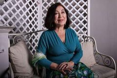 Mature Asian woman sitting on couch in luxurious dress Stock Photo