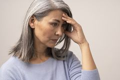 Mature Asian woman touches her forehead in distress. Upset Asian Woman Is Touching Her Forehead. Side View Of Tired Middle-Aged Woman Almost Crying And Covering stock photos