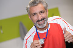 Mature athlete celebrating victory and showing off medal Stock Images