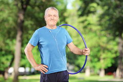 Mature athlete with headphones holding a hulahoop in park Stock Image