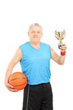 Mature athlete holding basketball and a trophy Stock Images