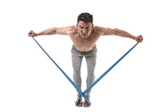 Mature athletic sport man with bodybuilder strong and fit body training doing exercises with elastic rubber band. 40s mature athletic sport man with bodybuilder Royalty Free Stock Photos