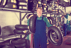 Mature attentive mechanic holding new tyre for motorcycle. In workshop Royalty Free Stock Image