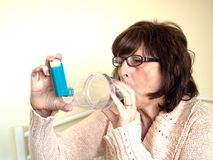 Mature attractive lady using asthmatic pump spacer device to ease condition. Mature attractive woman using pump spacer device for asthma medication to ease the royalty free stock photo