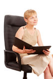 Mature attractive woman with folder in armchair Stock Images