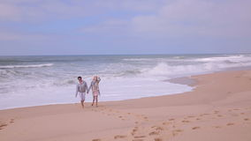 Mature attractive woman and her adult daughter walking on deserted beach. stock video footage