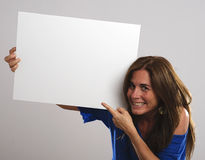 Mature attractive woman with long hair laughing  while holding a white sign Royalty Free Stock Photo