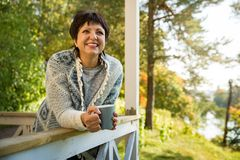 Mature attractive woman standing on terrace with cup of hot coffee. Wrapped up in knitted warm sweater. Lake house in autumn, yellow and red leaves on trees stock image
