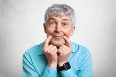 Mature attractive wrinkled male keeps fingers near lips, pretends smiling at camera, wears smart watch and shirt, isolated over wh. Ite concrete background Stock Image