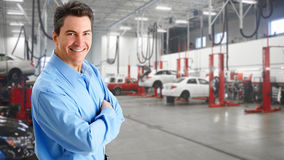Mature auto mechanic. Mature smiling auto mechanic over garage background Stock Images