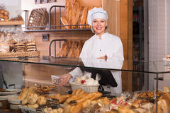 Mature bakery employee offering bread Stock Photo