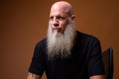 Mature bald man with long gray beard against brown background. Studio shot of mature bald man with long gray beard against brown background stock photography