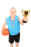 Mature basketball player holding a trophy Royalty Free Stock Image