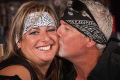Mature Bearded Man Kisses Woman. Smiling women in bandanna being kissed by handsome mature man Stock Image