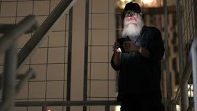 Mature bearded man looking suspicious while using phone. Portrait of mature bearded man looking suspicious at dark staircase stock video footage