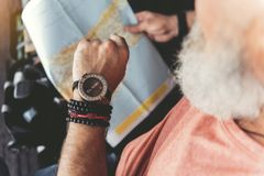 Mature bearded man waiting for flight. Elder tourist is holding map and checking time through wristwatch. Close up of male hand. Top view. Copy space on right Royalty Free Stock Image