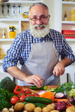 Mature bearded man wearing glasses posing at the camera while pr Stock Images