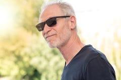 Mature bearded man wearing sunglasses, light effect Stock Images