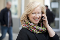 Mature beautiful blonde woman is calling on a cell phone Stock Photography