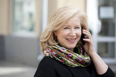 Mature beautiful blonde woman is calling on a cell phone Royalty Free Stock Photo