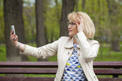Mature beautiful blonde woman is calling on a cell phone Royalty Free Stock Photos
