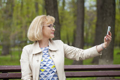 Mature beautiful blonde woman is calling on a cell phone Stock Photos