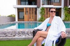 Mature beautiful Scandinavian tourist woman sitting near swimming pool in resort royalty free stock photography