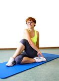Mature, beautiful woman in yellow shirt doing yoga Stock Photography