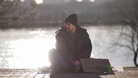 Mature beggar asking for money help on street. Mature beggar man sitting on pavement at river bank with cardboard sign asking for help. Bearded homeless man in stock footage
