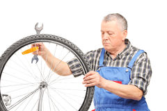 Mature bicycle mechanic looking at a wheel Stock Images