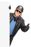 Mature biker giving thumb up behind a panel Stock Image