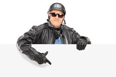 Mature biker pointing on a blank panel Stock Image