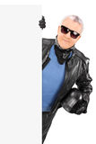 Mature biker posing behind a blank billboard Stock Photography