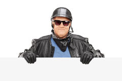 Mature biker standing behind a blank billboard. Isolated on white background Stock Photo