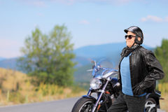 Mature biker walking in front of his motorbike Stock Image