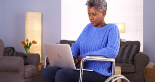 Mature Black woman sitting in wheelchair with laptop Stock Image