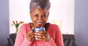 Mature black woman smiling with coffee mug. Senior black woman smiling with coffee mug Stock Photography