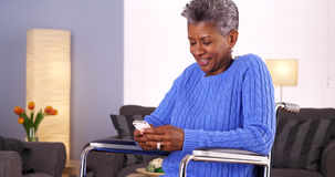 Mature black woman texting on smartphone Royalty Free Stock Images