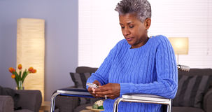 Mature black woman texting on smartphone Royalty Free Stock Photo