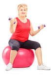 Mature blond female sitting on a fitness ball and exercising. With dumbbells isolated on white background Stock Photography