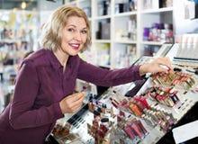 Mature blond woman choosing lip plumper on display Stock Images