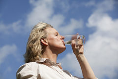 Mature blond woman drinking water. A beautiful mature blond woman drinking a glass of water in the summer heat Royalty Free Stock Images