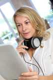 Mature blond woman with headphones and tablet Royalty Free Stock Image