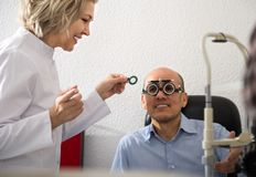 Mature blond woman ophthalmologist and a happy man retired eyesight check Stock Photos
