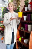 Mature blond woman selecting ceramic pot. Smiling mature blond woman selecting ceramic pot in flower store Stock Photography