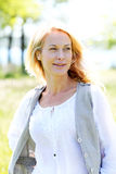 Mature blond woman standing in meadow field Royalty Free Stock Photos