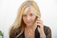 Mature blond woman talking on mobile phone Royalty Free Stock Photos