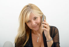 Mature blond woman talking on mobile phone Stock Photography