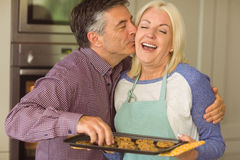 Mature blonde holding fresh cookies with husband kissing her Royalty Free Stock Photography
