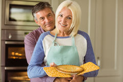 Mature blonde holding fresh pie with husband hugging her Stock Photography